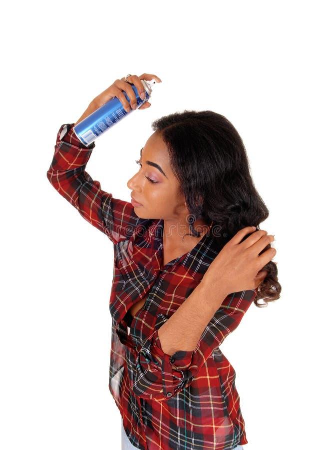 Mujer afroamericana que usa la laca para el pelo fotografía de archivo