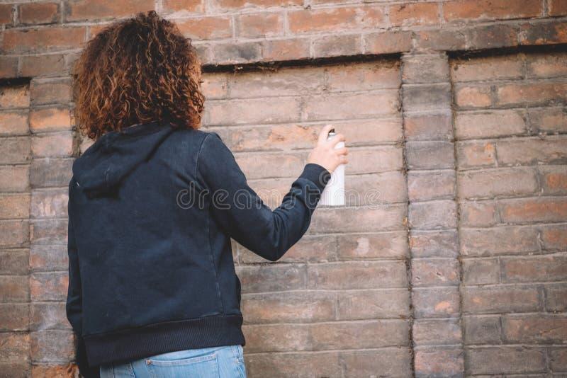 Mujer afroamericana que usa la pintura de espray imagen de archivo