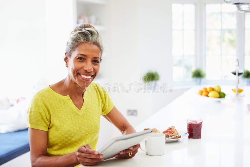 Mujer afroamericana que usa la tableta de Digitaces en casa foto de archivo