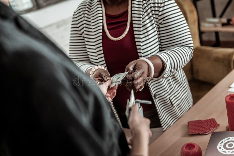 Mujer afroamericana regordeta en una chaqueta rayada que toma el dinero de un cliente imágenes de archivo libres de regalías