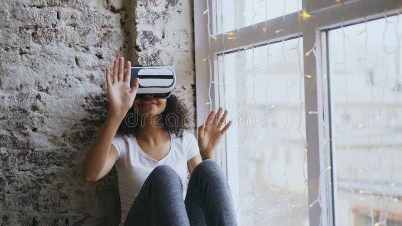 Mujer afroamericana rizada que consigue experiencia usando los vidrios de las auriculares de VR 360 de realidad virtual en casa imagenes de archivo