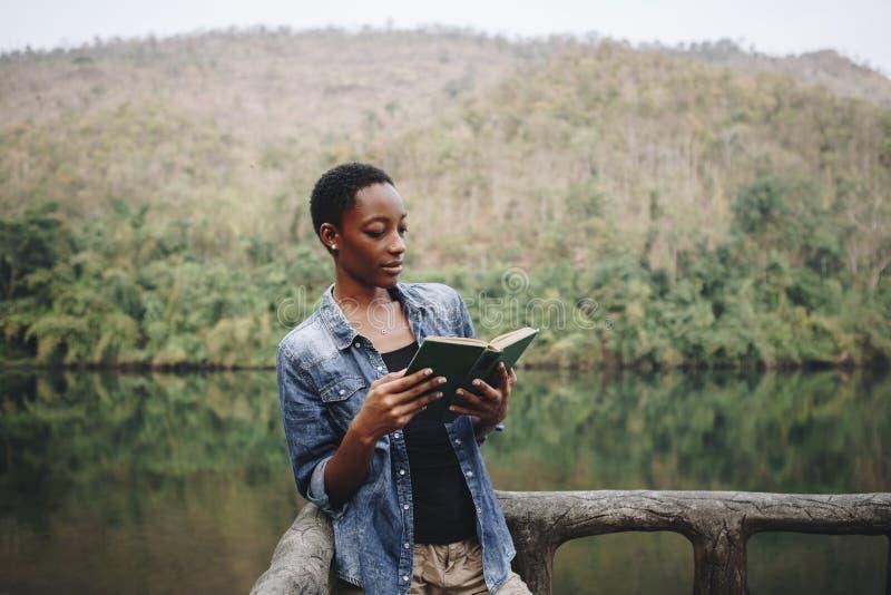 Mujer afroamericana solamente en la naturaleza que lee un concepto del ocio del libro imagen de archivo