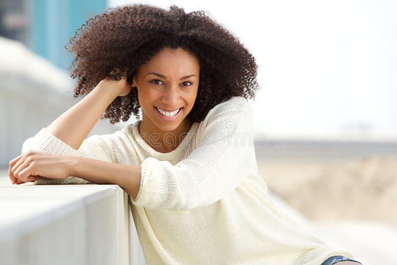 Mujer afroamericana sonriente con el pelo rizado que se sienta al aire libre imagen de archivo