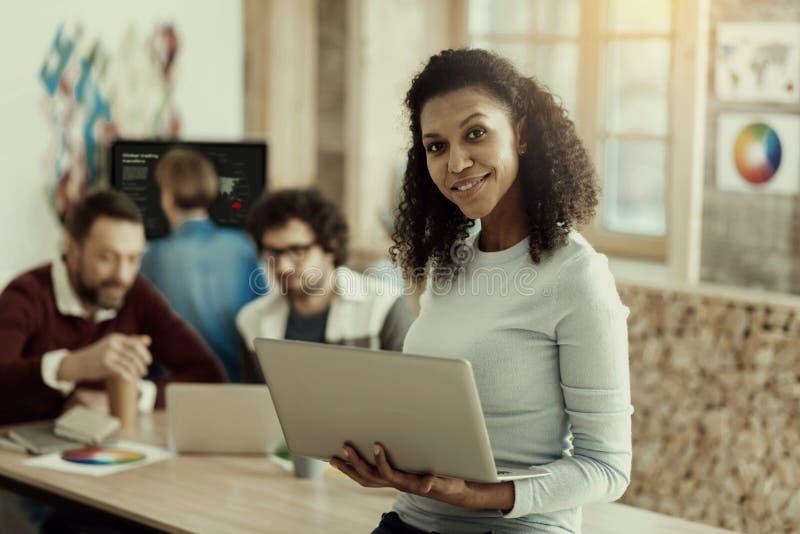 Mujer afroamericana sonriente con un positivo de la sensación del ordenador portátil fotografía de archivo libre de regalías