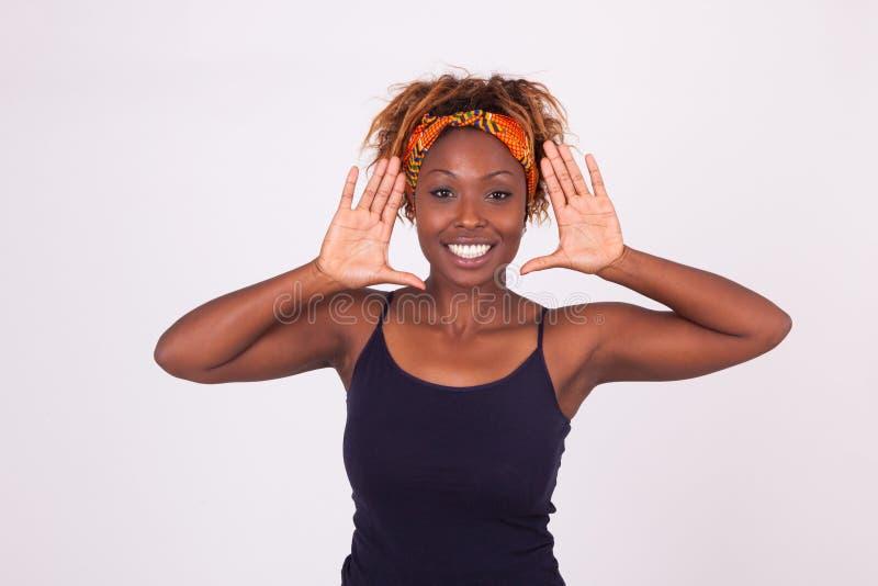 Mujer afroamericana sonriente hermosa que hace que el marco gesticula los wi imágenes de archivo libres de regalías