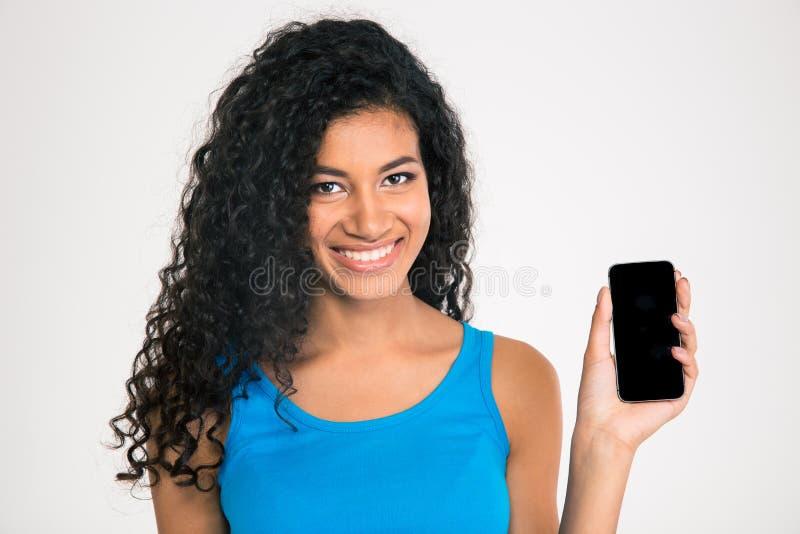 Mujer afroamericana sonriente que muestra la pantalla en blanco del smartphone imagenes de archivo