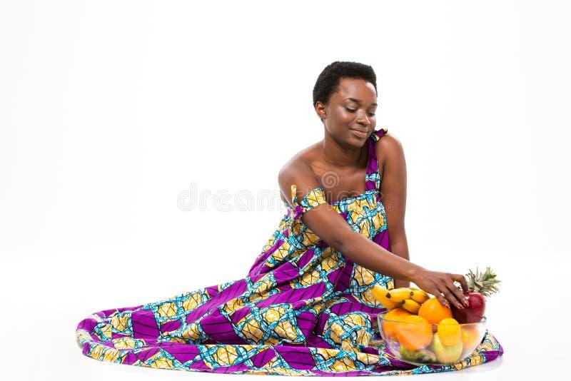 Mujer afroamericana sonriente que se sienta con el bol de vidrio de frutas fotos de archivo libres de regalías