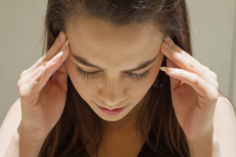Mujer agotada con el dolor de cabeza, jaqueca, tensión, resaca, menta imagen de archivo libre de regalías