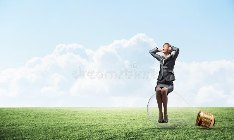 Mujer agotadora que se sienta en bombilla grande imagenes de archivo