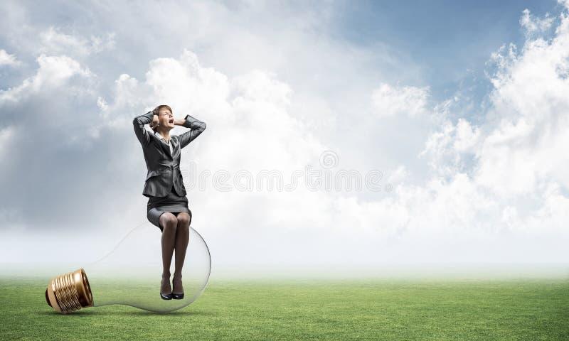 Mujer agotadora que se sienta en bombilla grande fotografía de archivo libre de regalías