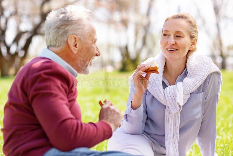 Mujer agradable alegre que come un bocadillo fotos de archivo
