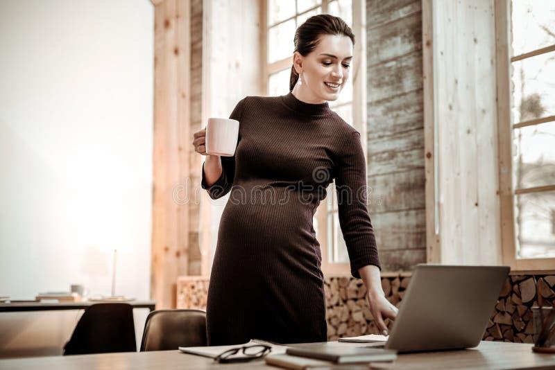 Mujer agradable alegre que presiona un botón en el ordenador portátil imágenes de archivo libres de regalías
