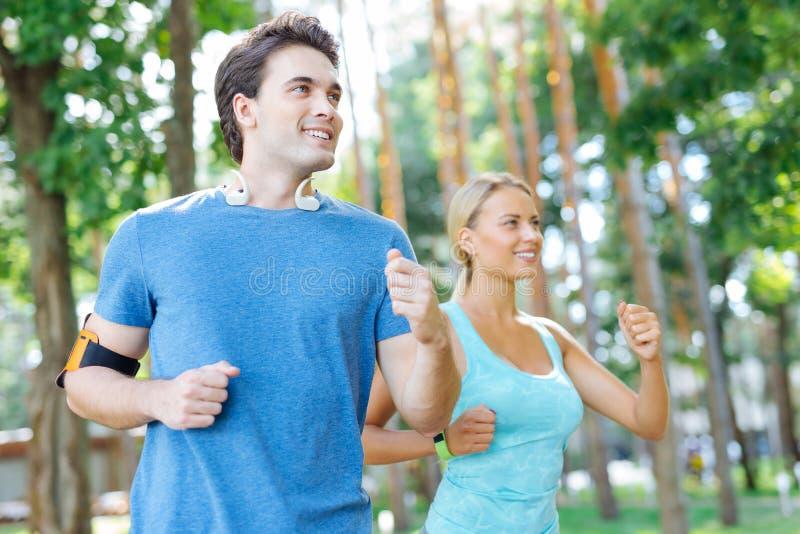 Mujer agradable encantada que corre con su novio imagenes de archivo