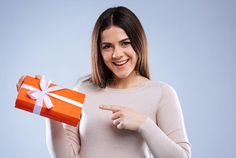 Mujer agradable feliz que señala en el presente imagen de archivo