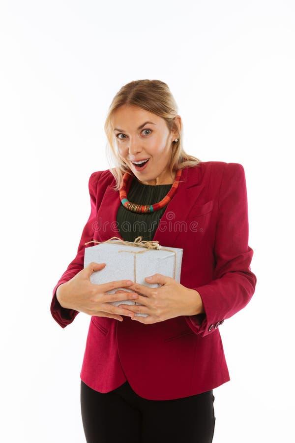Mujer agradable positiva alegre que lleva a cabo su presente imagenes de archivo
