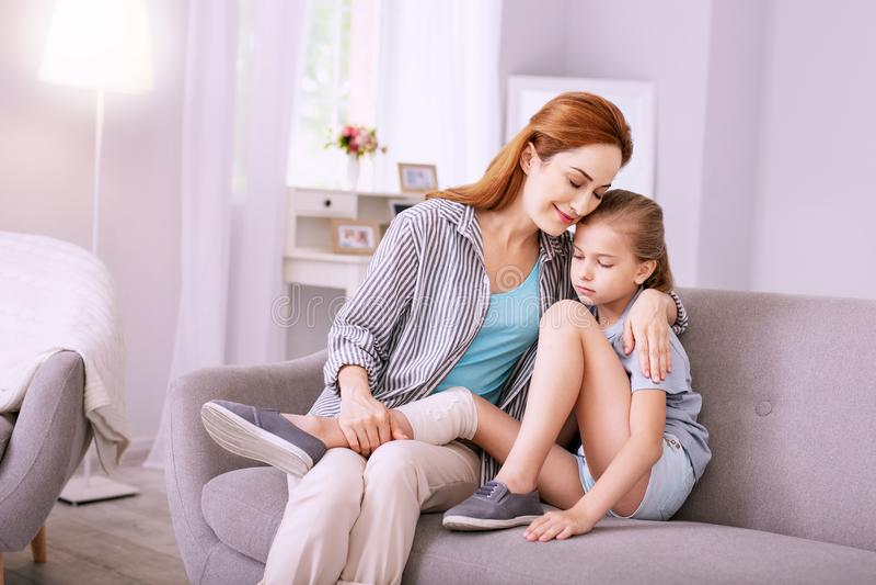 Mujer agradable positiva que abraza a su hija foto de archivo libre de regalías