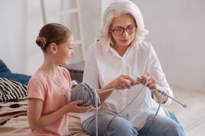 Mujer agradable positiva que enseña a su nieta a hacer punto fotografía de archivo libre de regalías