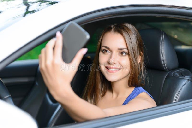 Mujer agradable que hace el selfie dentro del coche foto de archivo libre de regalías