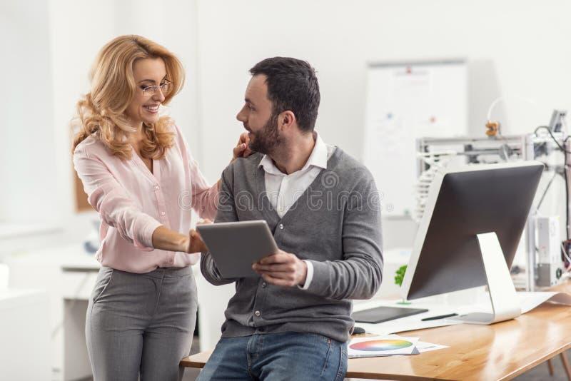 Mujer agradable que liga con su colega en la oficina imagen de archivo
