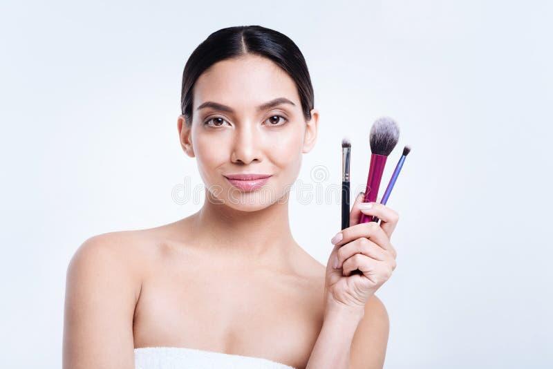 Mujer agradable que presenta con tres cepillos del maquillaje fotos de archivo libres de regalías