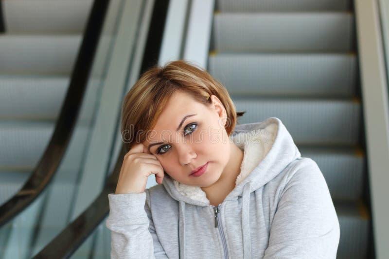 Mujer agradable regordeta hermosa en el fondo de la escalera móvil foto de archivo libre de regalías