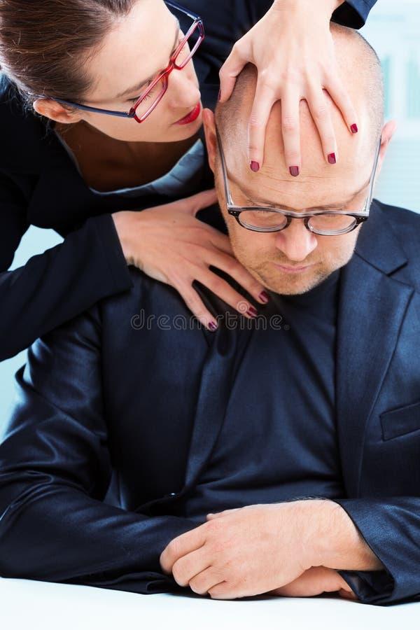 Mujer agresiva que atormenta al hombre en el lugar de trabajo fotografía de archivo libre de regalías