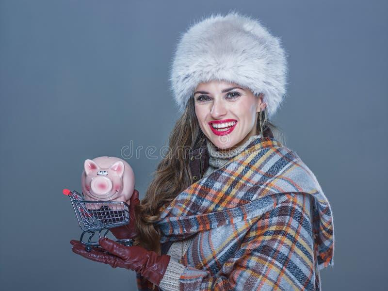 Mujer aislada en la carretilla azul fría de las compras que se sostiene con guarro imagenes de archivo