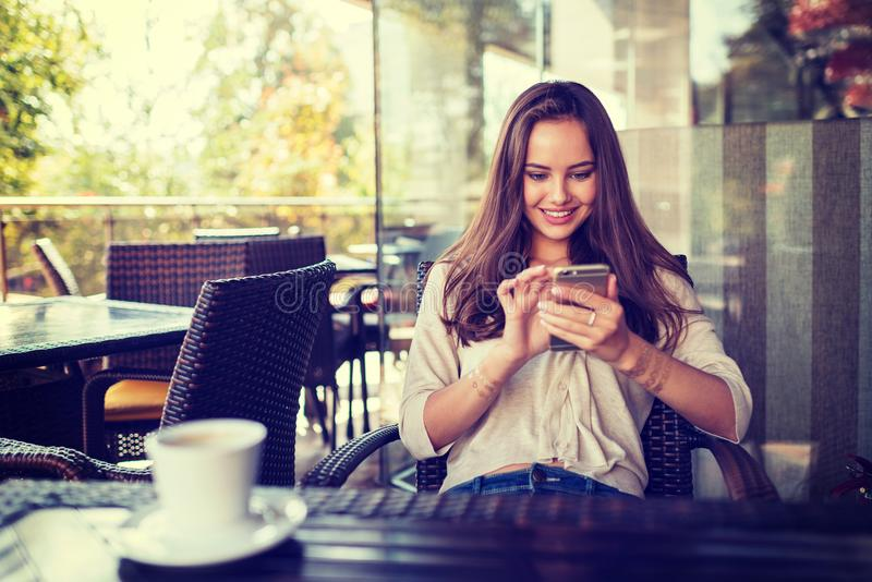 Mujer al café de consumición y usar del café su teléfono móvil imagen de archivo