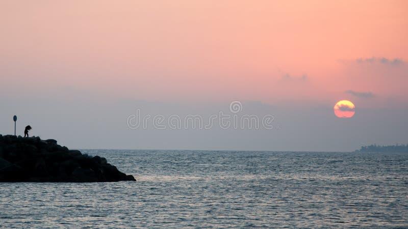 Mujer al lado del mar en la puesta del sol fotos de archivo libres de regalías