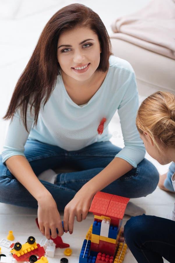 Mujer alegre agradable que juega con su hija foto de archivo