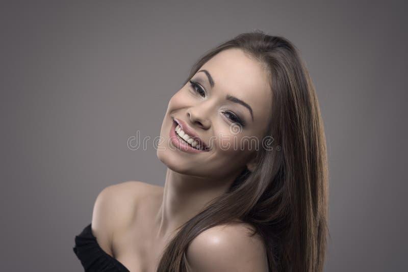 Mujer alegre bastante joven con sonrisa perfecta que sonríe y que mira la cámara con la cabeza titulada detrás foto de archivo libre de regalías