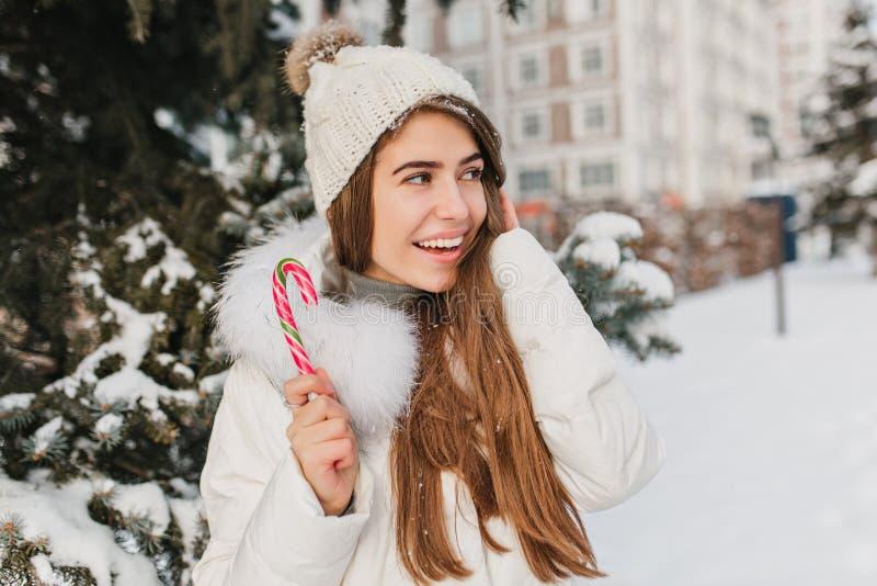Mujer alegre con el bastón de caramelo brillante largo de la tenencia del pelo y mirada lejos en fondo del árbol Foto al aire lib fotos de archivo