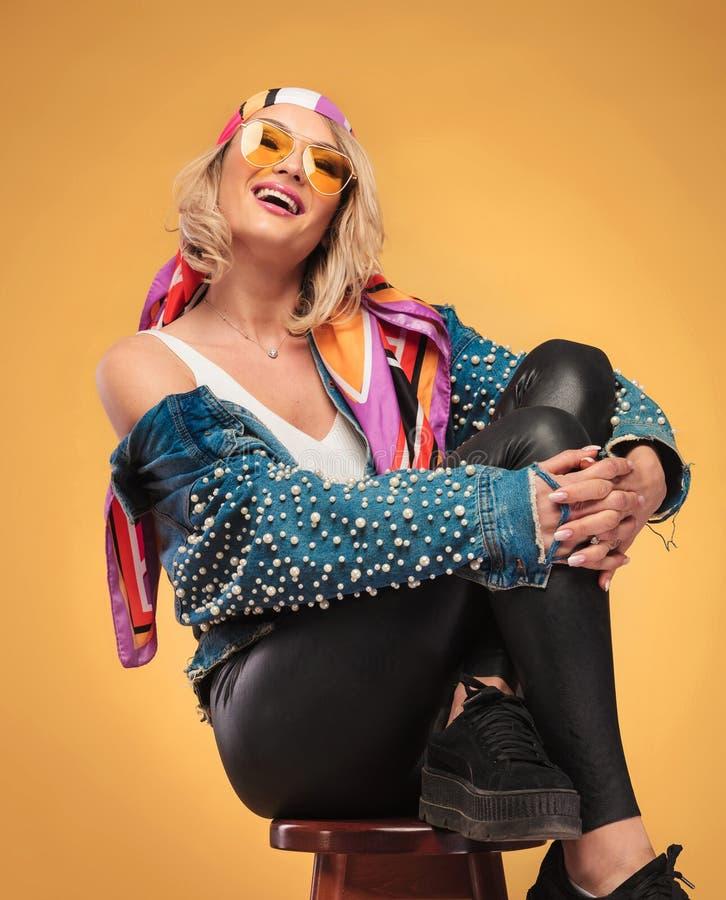 Mujer alegre con la ropa coloreada que se sienta mientras que abraza sus piernas foto de archivo libre de regalías