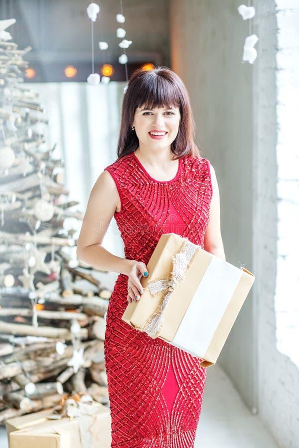 Mujer alegre con una caja de regalo La muchacha en vestido rojo Concepto o fotografía de archivo