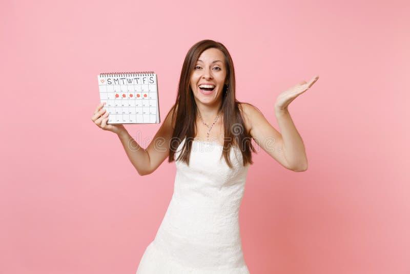 Mujer alegre de la novia en las manos de extensión del vestido de boda, sosteniendo el calendario femenino de los períodos para c imagen de archivo