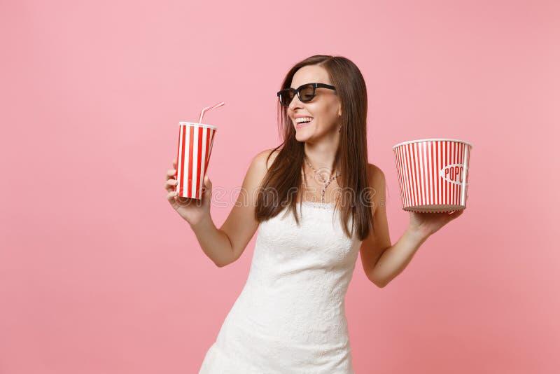 Mujer alegre de la novia en vestido de boda, los vidrios 3d mirando la película de cine, sosteniendo el cubo de palomitas, taza p imagen de archivo libre de regalías