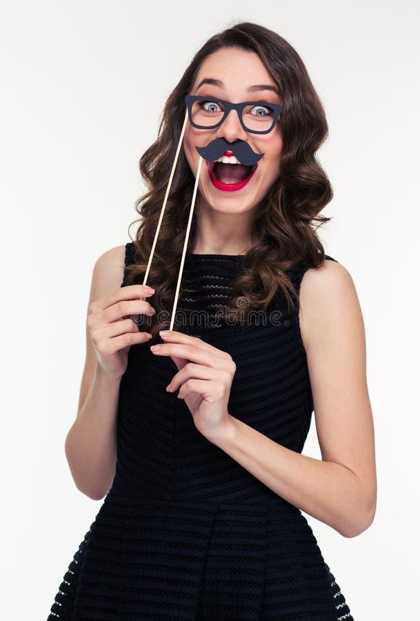 Mujer alegre divertida que se divierte usando los vidrios y los apoyos del bigote imagenes de archivo
