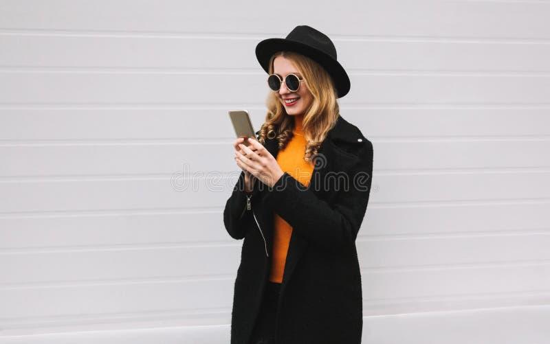 Mujer alegre elegante que mira el teléfono que lleva la chaqueta negra de la capa, sombrero redondo, gafas de sol en ciudad foto de archivo