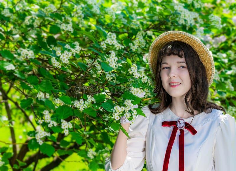 Mujer alegre en el vestido blanco cerca del espino floreciente imagenes de archivo