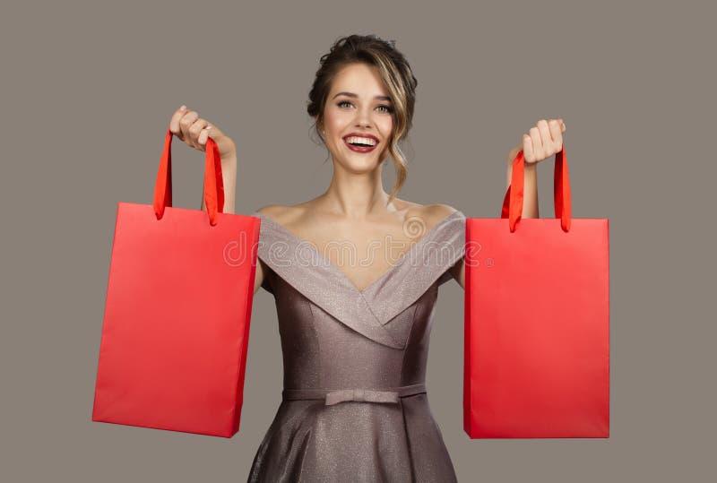 Mujer alegre en el vestido de noche que sostiene bolsos que hacen compras rojos imágenes de archivo libres de regalías