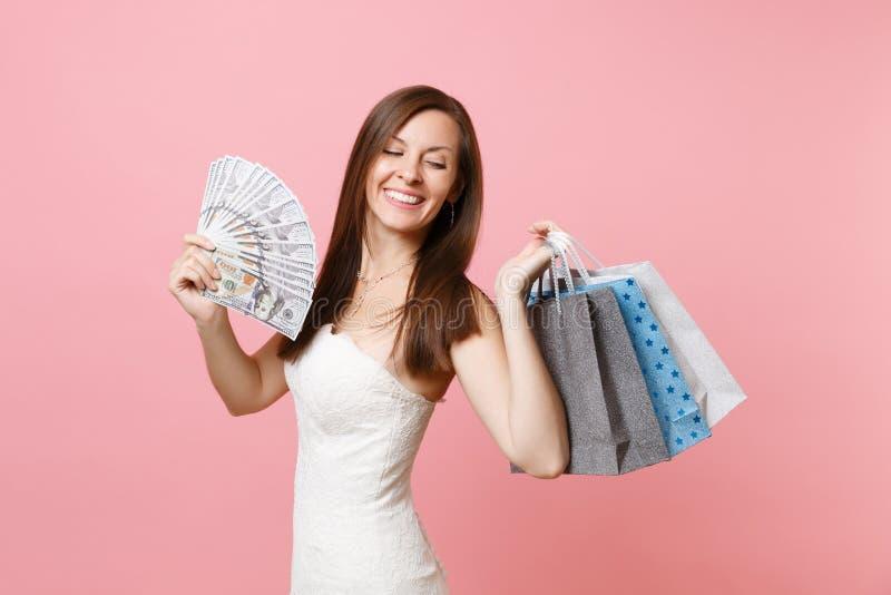 Mujer alegre en porciones del paquete del control del vestido de boda de dólares, dinero del efectivo, bolsos coloreados multi de foto de archivo