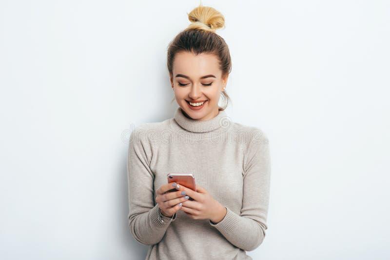 Mujer alegre alegre feliz con el maquillaje desnudo del bollo del pelo que lleva en el suéter que se coloca dentro con su smartph foto de archivo libre de regalías