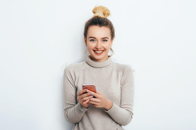 Mujer alegre feliz con el maquillaje desnudo del bollo del pelo que lleva en el suéter que se coloca dentro con su smartphone que imagen de archivo