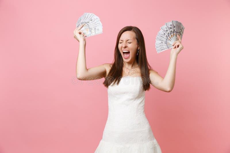 Mujer alegre feliz con los ojos cerrados en las porciones blancas del paquete del control del vestido que se casa de dólares, din imagen de archivo