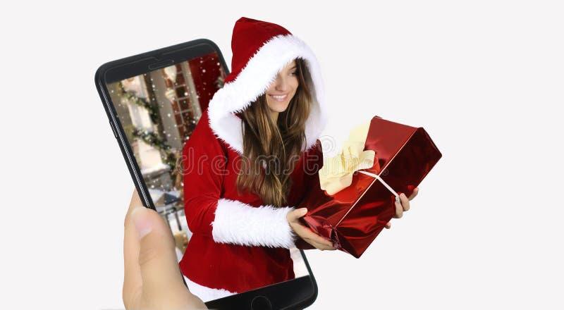 Mujer alegre feliz en el equipo rojo de Santa Claus que sale de un smartphone Concepto de la Navidad fotografía de archivo libre de regalías