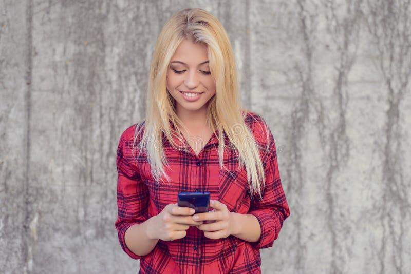 Mujer alegre feliz sonriente con el pelo rubio, en shir a cuadros fotografía de archivo