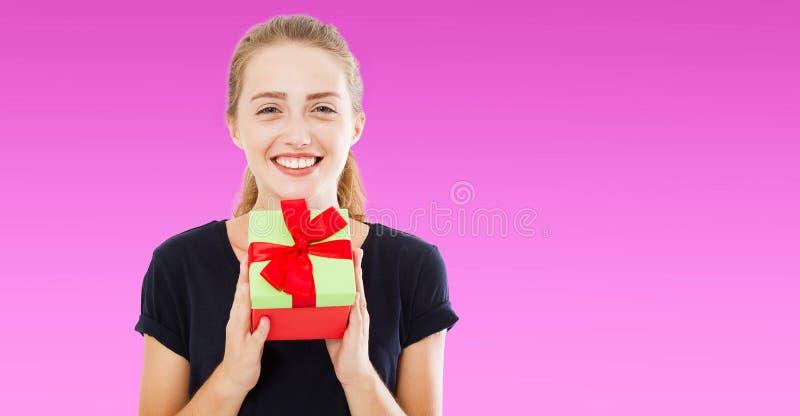 Mujer alegre hermosa en la camiseta negra que le da la actual caja sobre el fondo púrpura, días de fiesta concepto, espacio de la imagenes de archivo