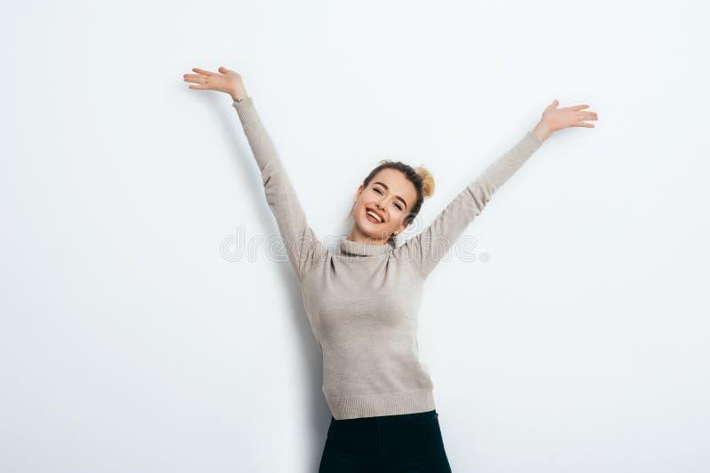 Mujer alegre hermosa joven con el bollo del pelo que lleva en vaqueros y el suéter que baila y que presenta sobre la pared blanca imagenes de archivo