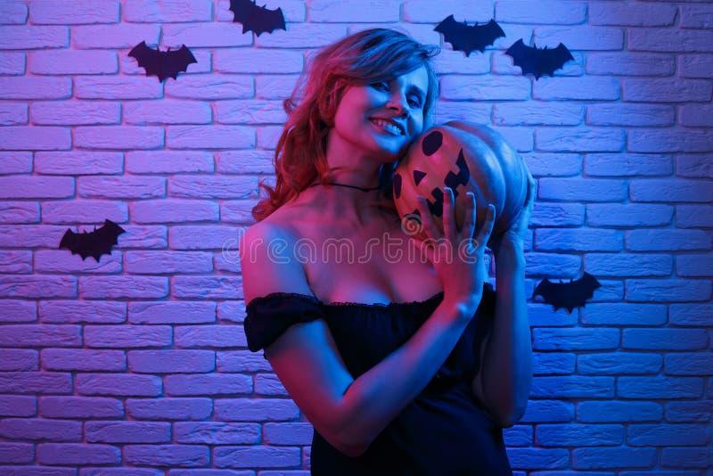 Mujer alegre hermosa joven con la calabaza en ir de fiesta de las manos H foto de archivo libre de regalías