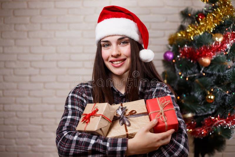Mujer alegre hermosa joven en el casquillo de Papá Noel con la caja de regalo de la abundancia foto de archivo libre de regalías